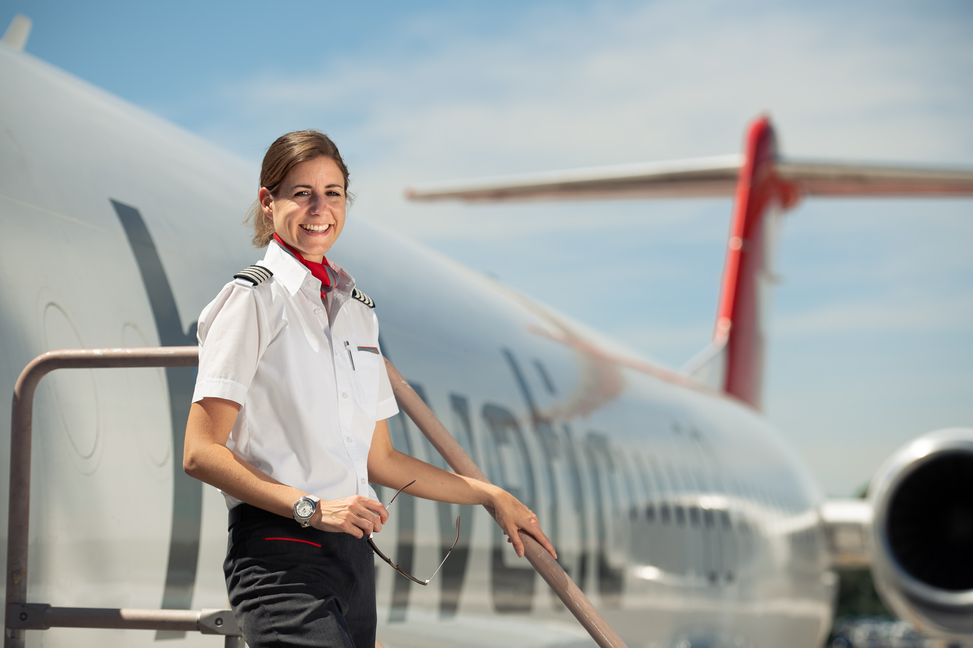Female Pilot Nadine Hachen in front of Helvetic Airways plane in Zurich Airport